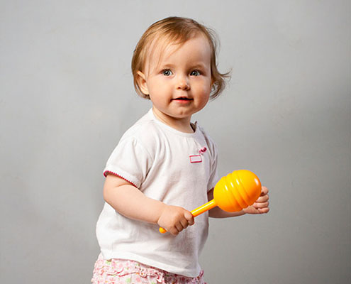 Beautiful baby girl with orange maraca.